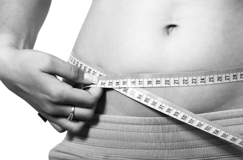 healthy weight loss: woman measuring waist